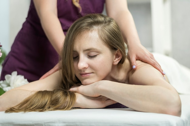 Beautiful happy woman lies in spa salon and enjoys professional massage. pleasant environment in beauty salon.