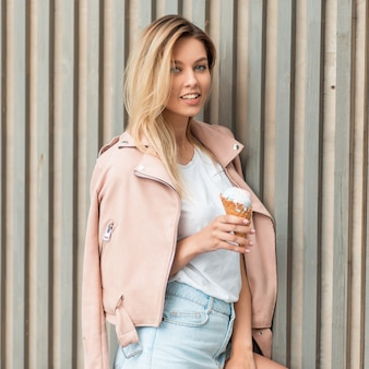 Beautiful happy woman model with a smile in a trendy pink jacket with a tasty ice cream near a wooden wall