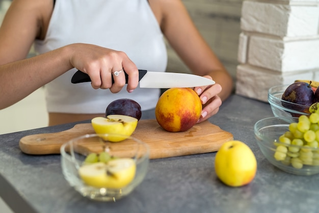 フルーツサラダを作るキッチンで美しい幸せな女性。健康食品の概念