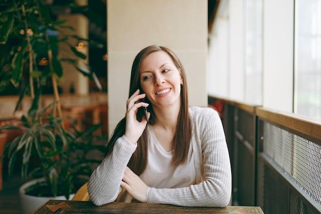 커피숍의 큰 창문 근처에 혼자 앉아 있는 아름다운 행복한 여성, 자유 시간 동안 레스토랑에서 휴식을 취합니다. 휴대 전화와 대화를 나누는 젊은 여성, 카페에서 휴식. 라이프스타일 컨셉