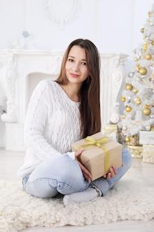 그녀의 손에 선물 크리스마스 트리 옆에 앉아 아름 다운 행복 한 여자