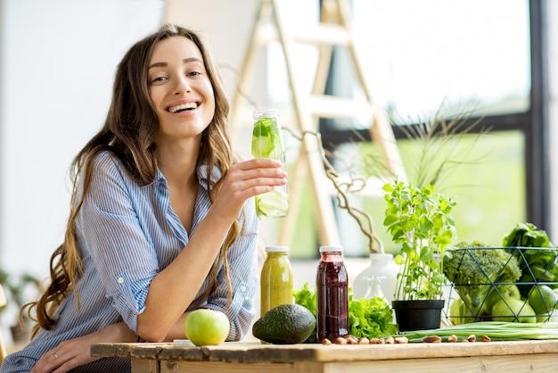 家で飲み物と健康的な緑の食べ物と一緒に座っている美しい幸せな女性。ビーガンミールとデトックスのコンセプト