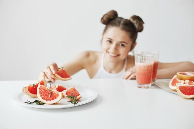 白い壁の上のテーブルに座っている皿からグレープフルーツのスライスを取って笑って幸せな美人。健康的なフィットネス食品。