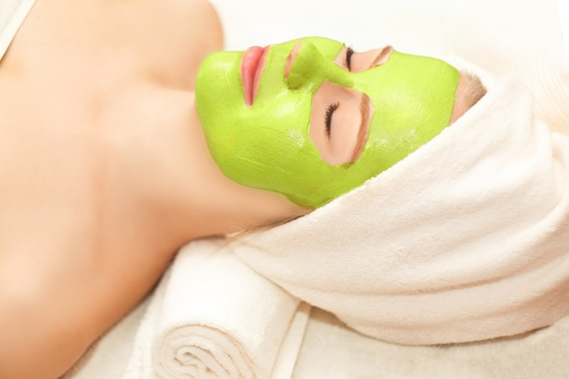 Beautiful happy woman in the spa making face mask treatment