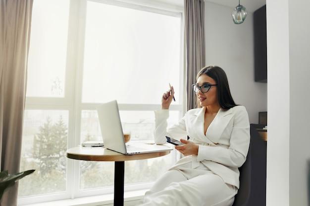 ノートパソコンで在宅勤務中に携帯電話を使用して美しい幸せな女性。スマートフォンでメッセージメッセージの眼鏡をかけている笑顔の女性。