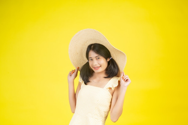 A beautiful, happy woman wearing a big hat showing cheerfulness on a yellow .