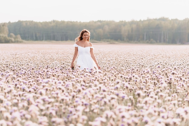 Beautiful happy woman in a white dress in a field of flowers in summer in nature