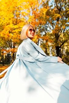 スタイリッシュなサングラスとファッションの青いコートを着たかわいい笑顔の美しい幸せな女性は、明るい黄色の紅葉の秋の公園を歩きます
