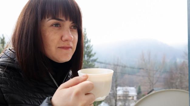 그녀의 호텔 방 발코니에서 아침 안개 속에서 산 풍경의 아름다운 전망을 즐기는 흰색 커피 또는 차 한잔과 함께 아름다운 행복한 여자. 가을과 겨울 여행 컨셉입니다.