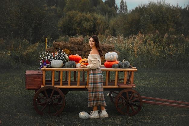 다채로운 호박과 나무 카트를 가진 아름 다운 행복 한 여자