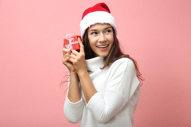 ピンクの背景にクリスマスプレゼントと美しい幸せな女