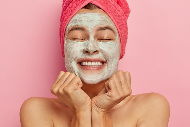 Beautiful happy woman with closed eyes, has clay mask on face, improves appearane, hydrates skin, smiles broadly, has white perfect teeth, feels being pampered like in spa, wears towel on wet hair