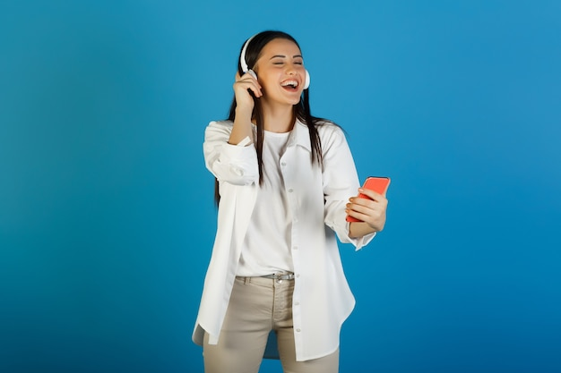 目を閉じて携帯電話で楽しく音楽を聴いているイヤホンを持つ美しい幸せな女性。