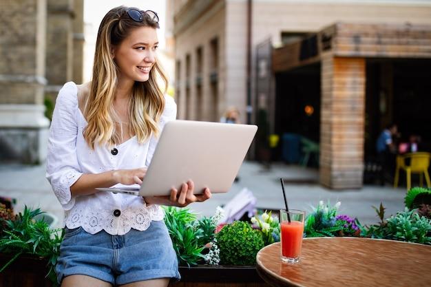 屋外のラップトップを持つ美しい幸せな女性。ピープルテクノロジーワーク楽しい研究コンセプト