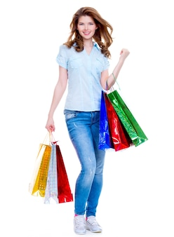 白い背景で隔離のブルージーンズの買い物袋を持つ美しい幸せな女性。