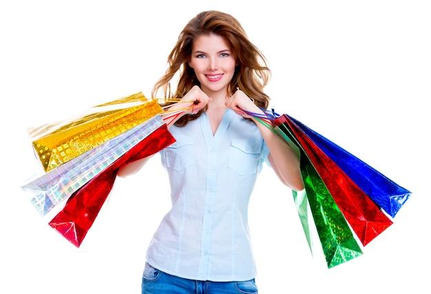 Красивая счастливая женщина с хозяйственными сумками в синих джинсах, изолированных на белом фоне.
