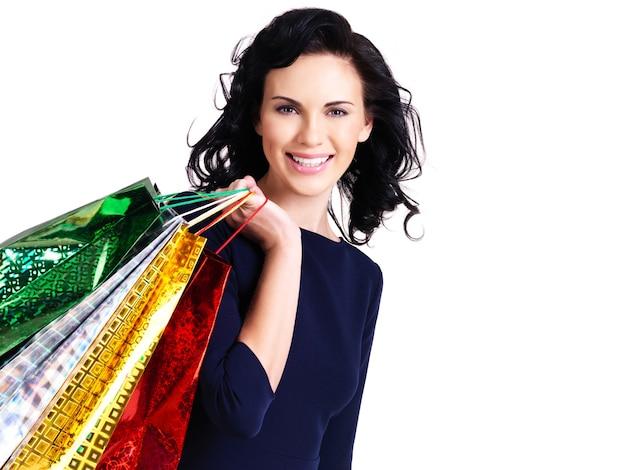 白い背景で隔離の買い物袋を持つ美しい幸せな女性。