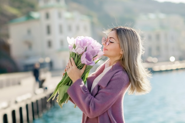 Beautiful happy woman with straight hair holding a bouquet of pink tulips