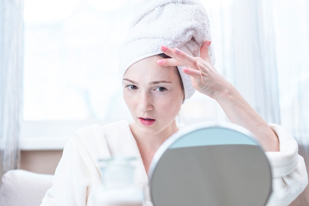 Beautiful happy woman with a towel on her head looking at her skin in a mirror. hygiene and care for the skin