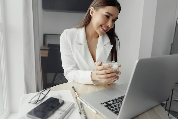 Beautiful happy woman working at home with laptop taking cup of coffee . smiling business woman woman  in office, using laptop computer
