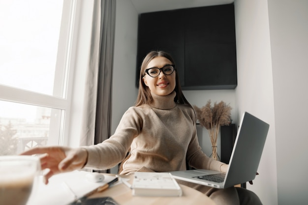 Beautiful happy woman working at home with laptop taking cup of coffee . smiling business woman woman wearing eyeglasses in office,  using laptop computer
