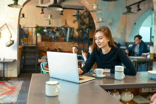 Beautiful happy woman working on laptop computer during coffee break in cafe bar