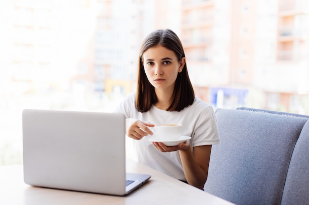 Красивая счастливая женщина работает на ноутбуке во время перерыва на кофе в кафе-баре