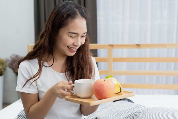 Beautiful happy yong woman eating breakfast with fruit and cake on bed