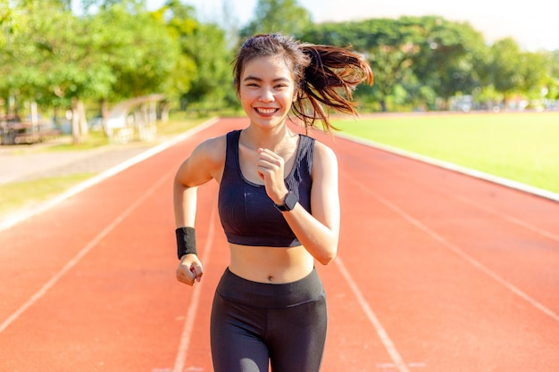 Beautiful happy young asian woman running for her morning exercise at a running track, healthy lifestyle