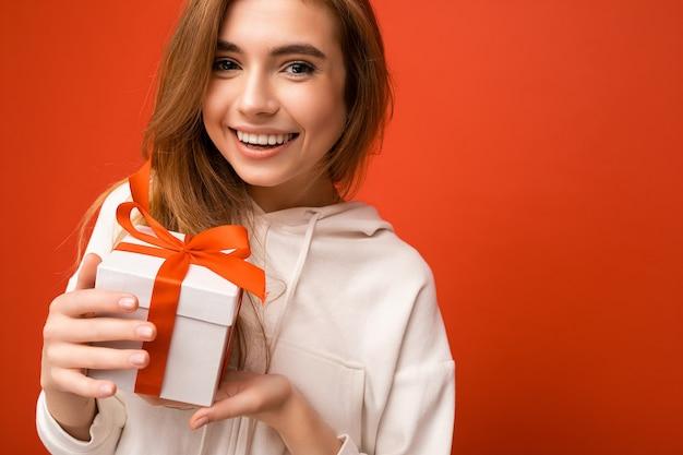 선물 상자를 들고 카메라를보고 세련된 캐주얼 옷을 입고 화려한 벽에 고립 된 아름 다운 행복 한 젊은 금발의 여자