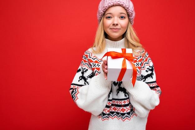 선물 상자를 들고 세련 된 캐주얼 옷을 입고 화려한 벽에 고립 된 아름 다운 행복 한 젊은 금발의 여자.