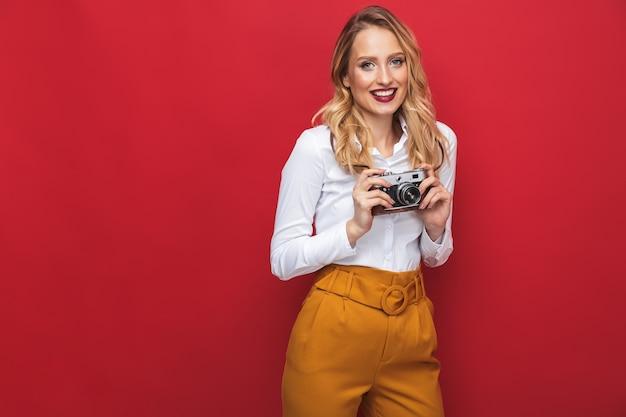 Красивая счастливая молодая блондинка женщина, стоящая изолирована на красном фоне, держа фотоаппарат
