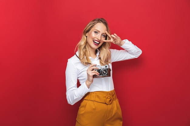 Beautiful happy young blonde woman standing isolated over red background, holding photo camera