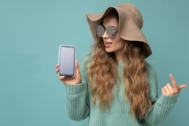 青い背景で隔離のサングラスと夏の帽子を身に着けている美しい幸せな若いブロンドの女性