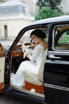Beautiful happy young bride and groom looking from retro auto
