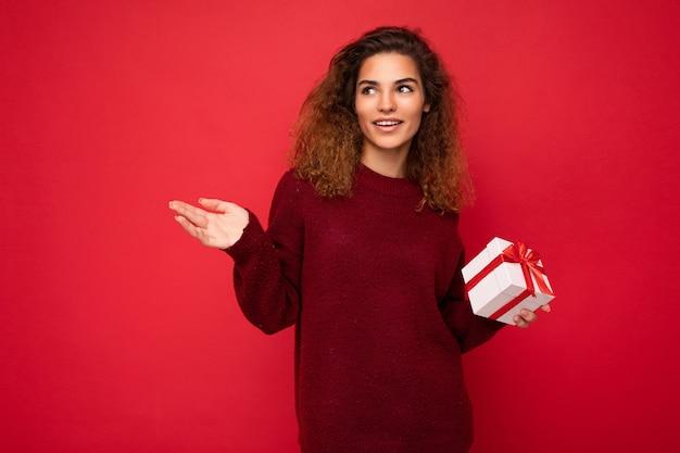 Красивая счастливая молодая брюнетка женщина изолирована над красочной второстепенной стеной в стильной повседневной одежде