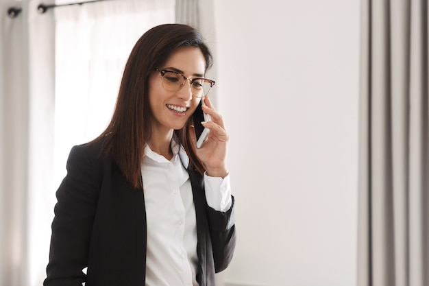 Beautiful happy young business woman in formal wear clothes indoors at home talking by mobile phone.