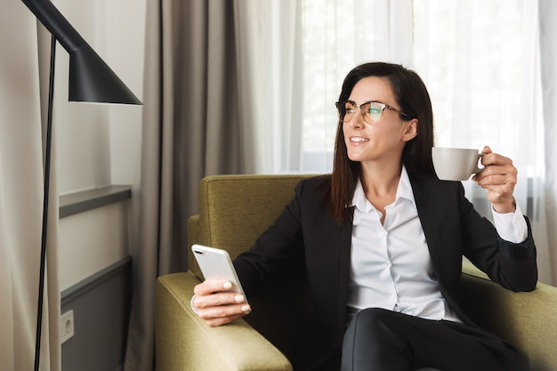 Beautiful happy young business woman in formal wear clothes indoors at home using mobile phone drinking coffee.
