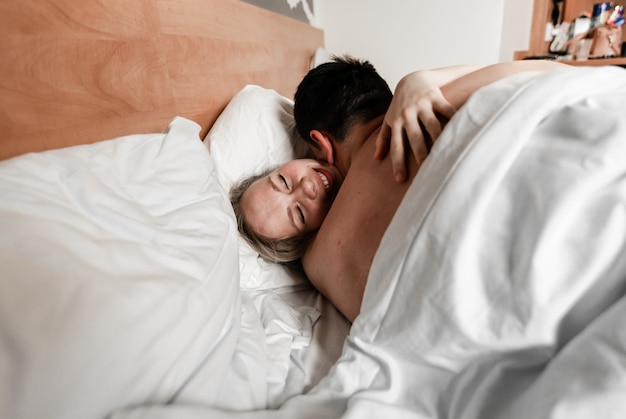 Beautiful happy young couple or family waking up together in bed
