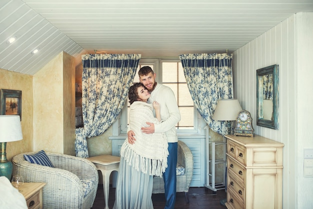 Beautiful and happy young couple man and woman at home in a cozy white interior