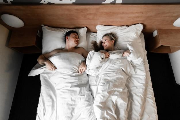 Красивая счастливая молодая пара или семья просыпается вместе в постели