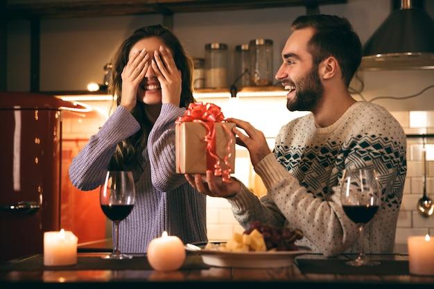 家でロマンチックな夜を一緒に過ごし、赤ワインを飲み、プレゼントを与える男を過ごす美しい幸せな若いカップル