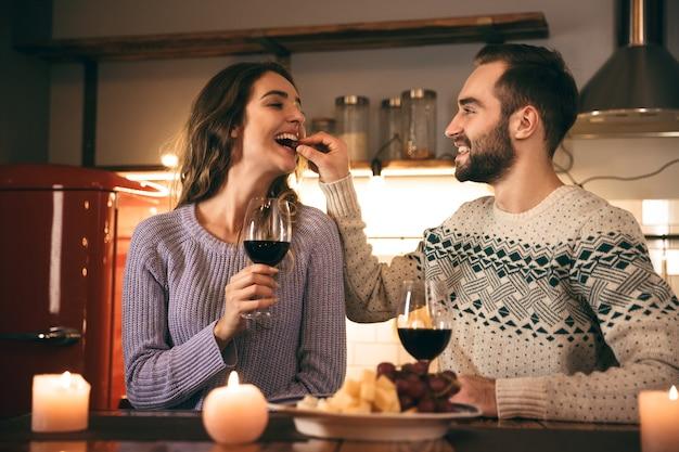 家でロマンチックな夜を一緒に過ごし、赤ワインを飲み、乾杯する美しい幸せな若いカップル
