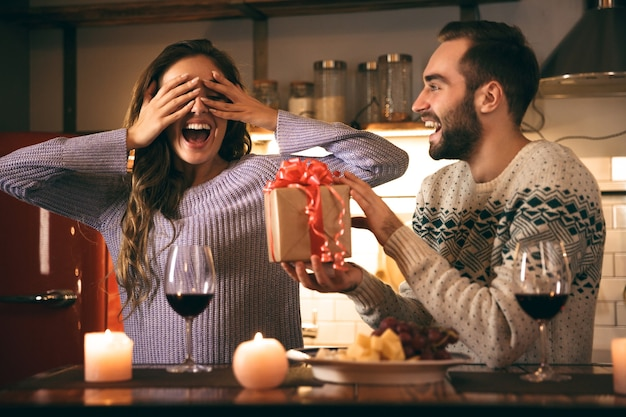 Beautiful happy young couple spending romantic evening together at home, drinking red wine, man giving a present