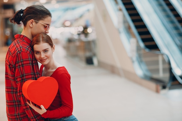 Beautiful happy young couple with shopping bags in shopping mall escalator.
