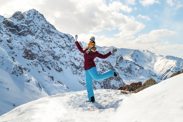 Beautiful happy young dancing woman on top of the mountain