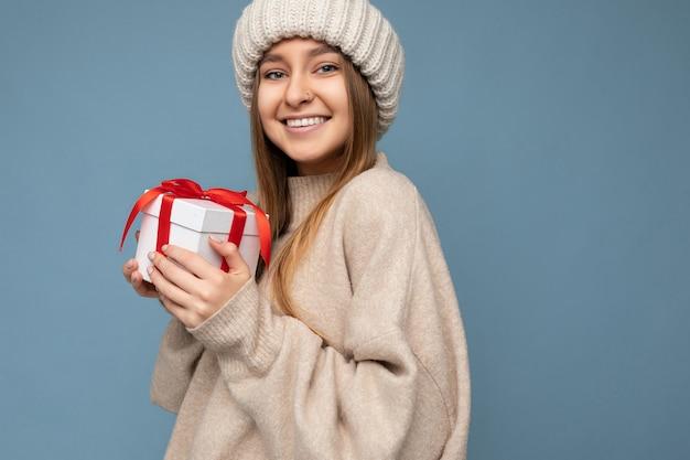 Красивая счастливая молодая темная блондинка женщина изолирована над красочной стеной в стильной повседневной одежде, держит подарочную коробку и смотрит в камеру