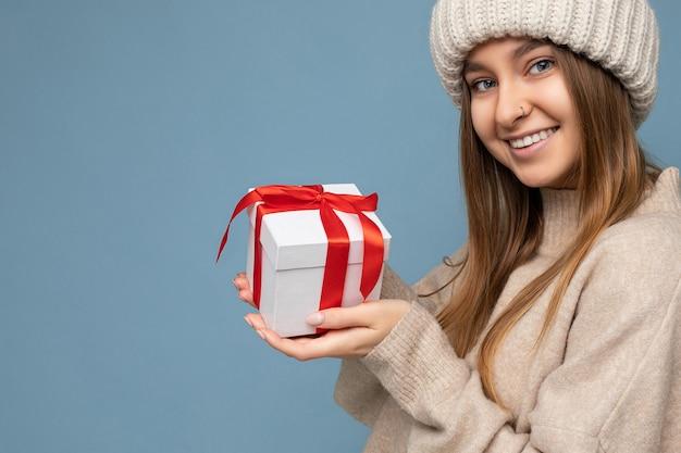 선물 상자를 들고 카메라를 찾고 세련된 캐주얼 옷을 입고 화려한 벽 위에 절연 아름 다운 행복 한 젊은 어두운 금발의 여자
