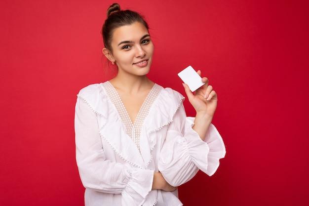 카메라를 보고 신용 카드를 들고 빨간 배경 위에 고립 된 흰색 블라우스를 입고 아름 다운 행복 한 젊은 어두운 금발 여자
