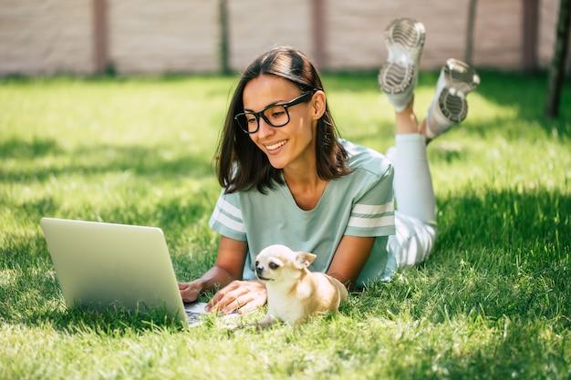 彼女の小さなかわいい犬と一緒に美しい幸せな若いフリーランスの女性は、屋外のラップトップに取り組んでいます。